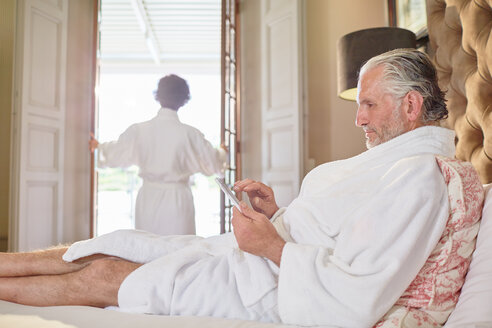 Mature man in spa bathrobe using digital tablet on hotel bed - CAIF23150