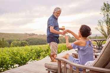 Mature couple drinking champagne on deck - CAIF23153