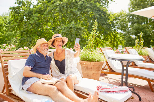 Happy mature couple taking selfie with camera phone at sunny resort poolside - CAIF23159