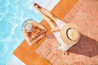 View from above mature couple relaxing at sunny swimming pool - CAIF23168