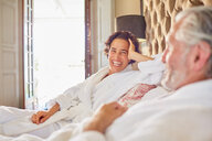Happy, laughing mature couple relaxing on hotel bed - CAIF23174