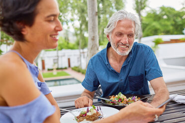 Mature couple dining at patio table - CAIF23177