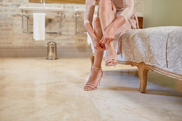 Woman putting on high heel sandals in luxury bathroom - CAIF23183