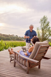 Mature couple relaxing, toasting champagne flutes on resort patio - CAIF23189