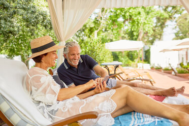 Mature couple relaxing, using smart phone on lounge chairs in resort cabana - CAIF23192