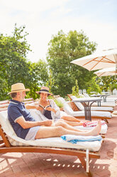 Mature couple relaxing, reading on lounge chairs at sunny resort poolside - CAIF23195