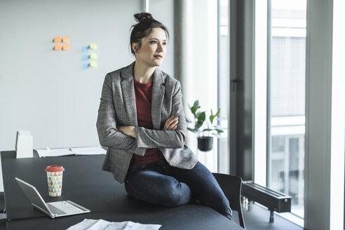 Businesswoman sitting on desk in office looking sideways - UUF17082