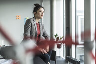Businesswoman sitting on desk in office looking out of window - UUF17085