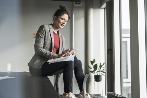 Businesswoman sitting on desk in office using cell phone - UUF17088