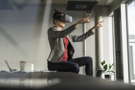 Businesswoman sitting on desk in office wearing VR glasses - UUF17091