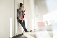 Businesswoman leaning against a wall in office using cell phone - UUF17094