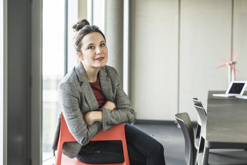 Portrait of smiling businesswoman sitting on chair in office - UUF17100