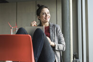 Smiling businesswoman sitting on chair in office with laptop looking sidways - UUF17106
