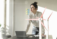 Businesswoman with wind turbine models and laptop on desk in office - UUF17109