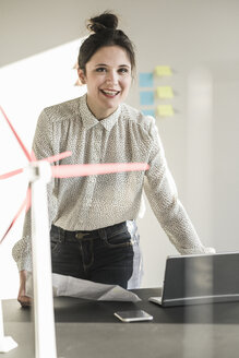 Portrait of smiling businesswoman with wind turbine model on desk in office - UUF17112