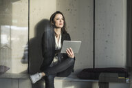 Businesswoman with tablet sitting in lounge area in office - UUF17124