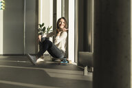 Smiling businesswoman sitting on skateboard at the window in office - UUF17127