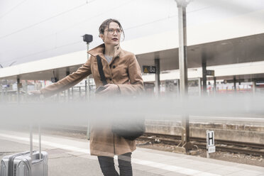 Businesswoman with baggage on station platform - UUF17136