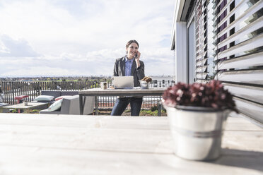 Smiling businesswoman with cell phone and laptop on roof terrace - UUF17139