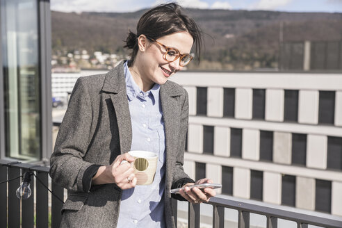 Smiling businesswoman with cell phone and cup of coffee on roof terrace - UUF17145