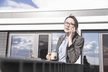 Businesswoman on cell phone on roof terrace - UUF17148