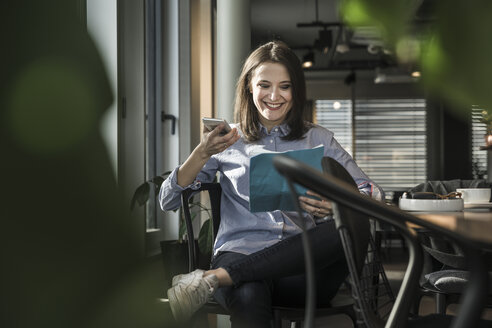 Smiling businesswoman sitting in office with paper and cell phone - UUF17151