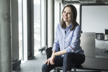 Smiling businesswoman sitting on conference table in office - UUF17154