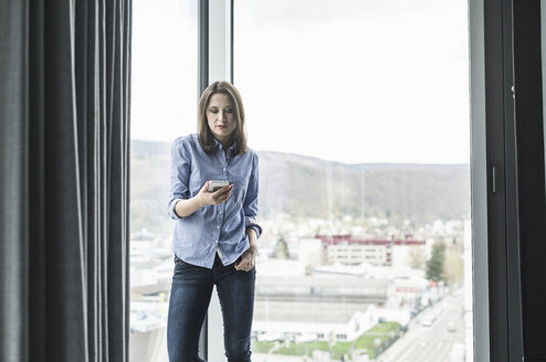 Businesswoman with cell phone standing at the window in office - UUF17160