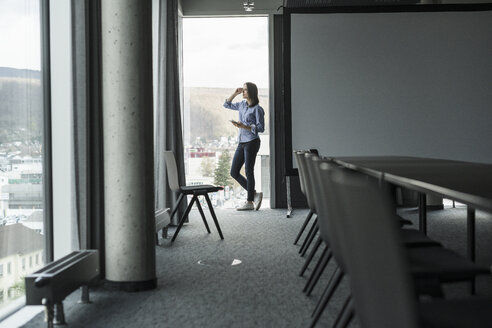 Businesswoman with cell phone standing at the window in office - UUF17163
