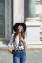 Italy, Florence, portrait of happy young tourist with camera - MGIF00334