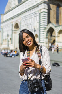 Italy, Florence, portrait of happy young tourist with camera and backpack using smartphone - MGIF00337