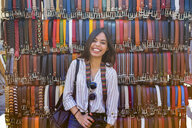 Italy, Florence, portrait of laughing young tourist with backpack and camera on street market - MGIF00340