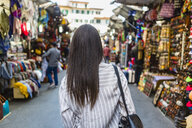 Italy, Florence, back view of young tourist exploring street market - MGIF00343