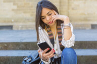 Italy, Florence, portrait of young tourist sitting on stairs listening music with earphones and smartphone - MGIF00346