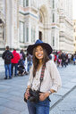 Italy, Florence, Piazza del Duomo, portrait of happy young tourist with camera - MGIF00352