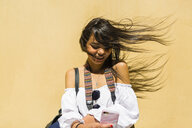 Portrait of smiling young woman with blowing hair in front of yellow background - MGIF00367