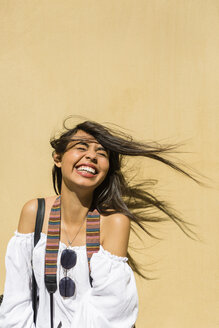Portrait of laughing young woman with blowing hair in front of yellow background - MGIF00370