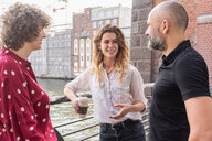 Man and female friends talking, river and buildings in background, Berlin, Germany - CUF49953