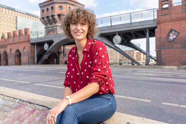 Young woman resting on Oberbaum bridge in city, Berlin, Germany - CUF49956