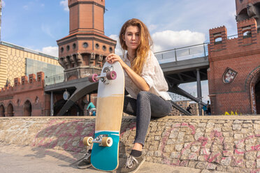 Young woman with skateboard resting on Oberbaum bridge in city, Berlin, Germany - CUF49959