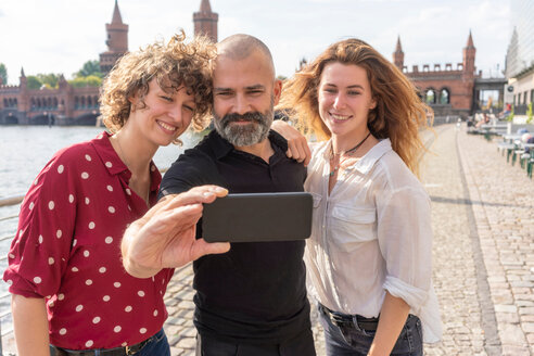 Man and female friends taking selfie with smartphone on bridge, river and buildings in background, Berlin, Germany - CUF49962