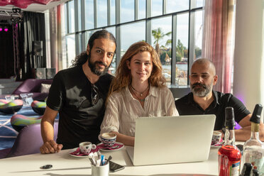 Group of three entrepreneurs using laptop and having coffee in office - CUF49965