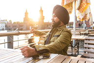 Indian man exploring city, river in background, Berlin, Germany - CUF49983
