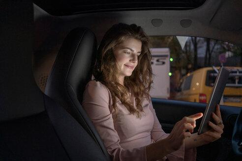 Young woman using digital tablet inside car - CUF49998