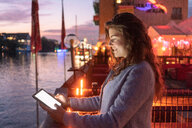 Young woman using digital tablet on bridge, river and city in background, Berlin, Germany - CUF50001