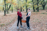 Best friends collecting chestnuts, Rezzago, Lombardy, Italy - CUF50037