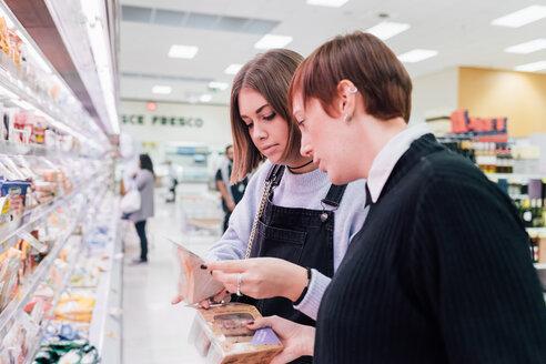 Women choosing food beside supermarket refrigerator - CUF50055