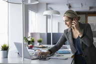 Female interior designer talking on smart phone at laptop in office - HEROF35438