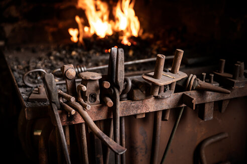 Row of tools in front of fire in blacksmiths workshop - CUF50063