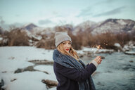 Woman in knitted hat holding sparkler on snow covered riverbank, portrait,  Orta, Piemonte, Italy - CUF50078